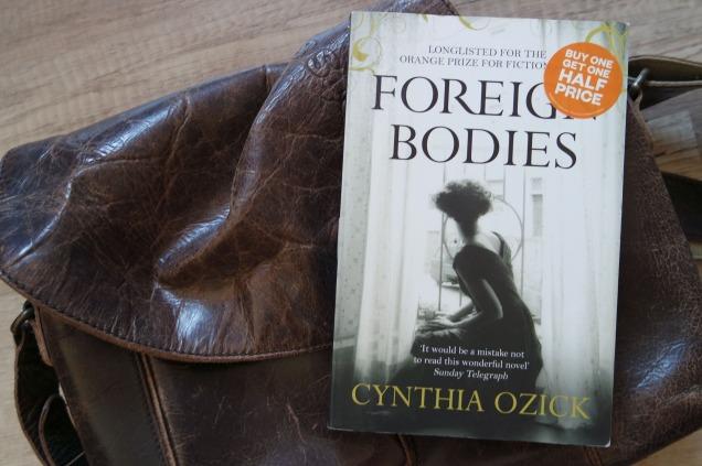 Das Cover von Cynthia Ozicks Foreign Bodies. Zu sehen ist eine Frau in einem eleganten Kleid, die aus dem Fenster auf eine Straße schaut.